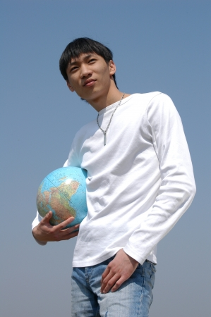 Young Asian man holding a terrestrial globe photo