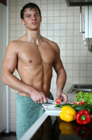 sexy food: Young muscular sexy man preparing salad at the kitchen Stock Photo