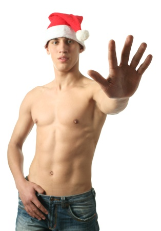 Young sexy man in Santa Claus hat holding his palm up isolated on white photo