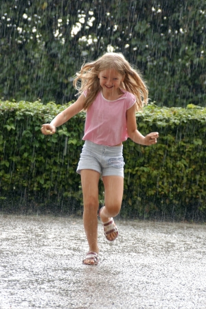sudden: Young girl running in the heavy rain in the park