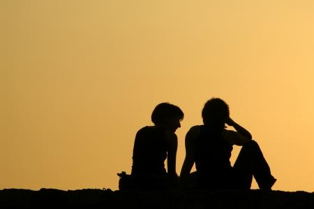 amistad: Siluetas de dos ni�as hablando a la puesta del sol