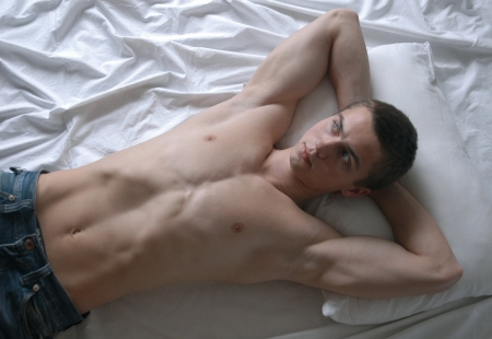 Young sexy man lying on a bed photo