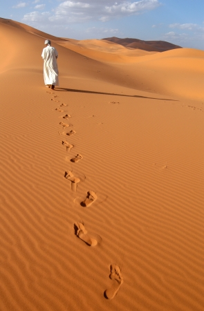 Lonely Berber man going ahead through the Sahara Desert in Morocco