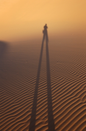 Human shadow in the sand dunes of Erg Chebbi in the Sahara Desert, Morocco  photo