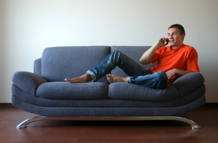 Sexy young man talking on the cell phone sitting on the sofa photo