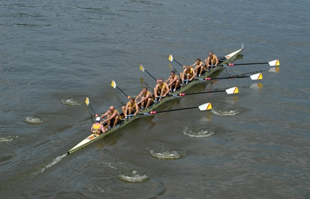 enforce: Rowing team rowing ahead during a boat-race on the River Vltava in Prague, Czech Republic Editorial