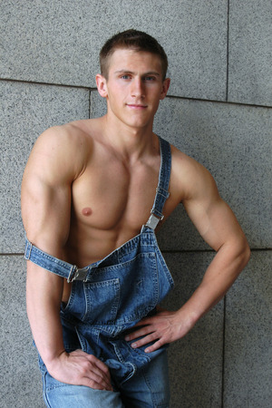 overalls: Young muscular worker in a blue coverall leaning on the stonewall Stock Photo