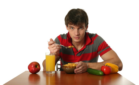 Young sexy man eating his breakfast isolated on white photo