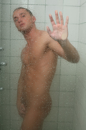 naked man: Young sexy man taking shower Stock Photo