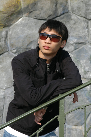 leaning by barrier: Young Asian man leaning against a fence Stock Photo