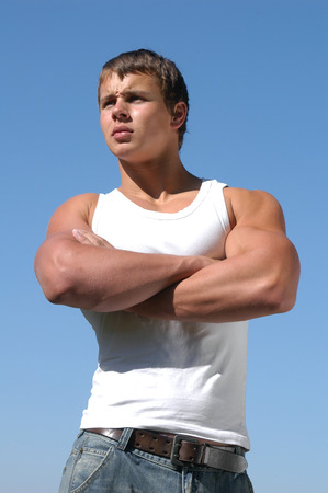 Young muscular athlete in a white sleeveless shirt photo