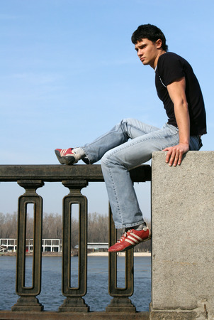 waiting glance: Young male model sitting on the embankment balustrade