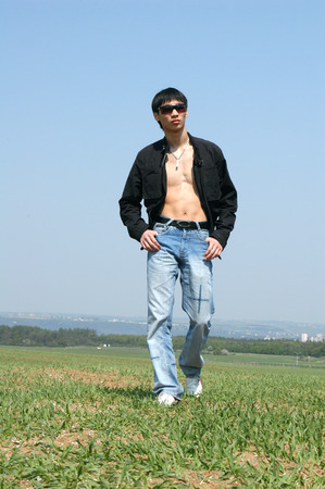 Young Asian man walking through the meadow photo