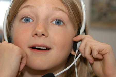 foreigner: Young girl learning foreigner language with a headset and a microphone