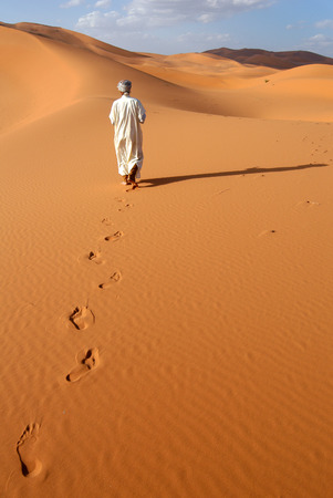 going places: Lonely Berber man going ahead through the Sahara Desert in Morocco