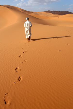 erg: Lonely Berber man going ahead through the Sahara Desert in Morocco