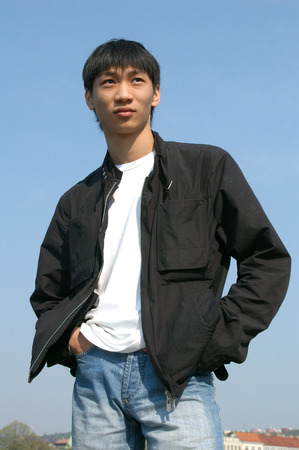 waiting glance: Young Asian man in a black jacket Stock Photo