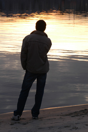 Young man on the riverbank at sunset photo