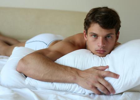 thin man: Hombre sexy acostado en una cama