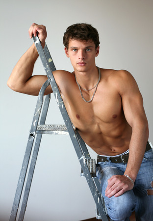 only the biceps: Sexy muscular man leaning on a stepladder Stock Photo