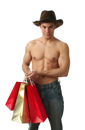 Young muscular man with shopping bags wearing a cowboy hat isolated on white photo