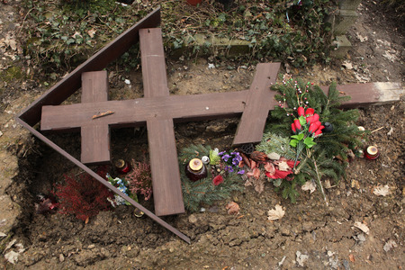 unmarked: Fallen orthodox cross on an unmarked grave at the Olsany Cemetery in Prague, Czech Republic.