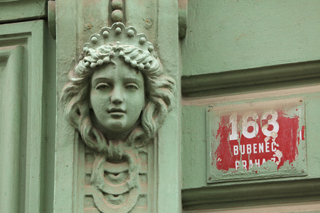 heads old building facade: Mascaron on the Art Nouveau building in Prague, Czech Republic.