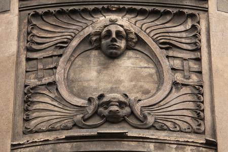 heads old building facade: Floral ornamental decoration and mascaron on the the Art Nouveau building in Prague, Czech Republic.