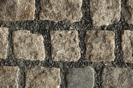 cobbled: Cobbled pavement made of granite cubes. Background texture. Stock Photo