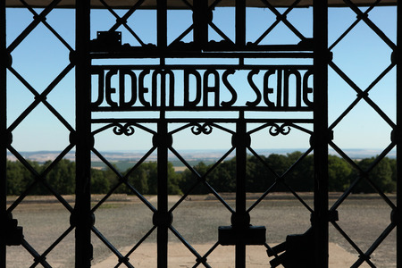 reich: WEIMAR, GERMANY - JUNE 21, 2013: Notorious Nazi motto Jedem das Seine (To Each His Own) seen on the main gate of the Buchenwald concentration camp near Weimar, Germany.