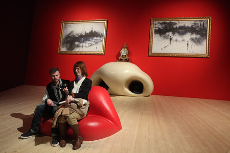 surrealist: PARIS, FRANCE - JANUARY 7, 2013: Visitors take a picture as they sit at the Mae West Lips Sofa inside the installation Mae West Face (1934) by Spanish surrealist artist Salvador Dali displayed at his retrospective exhibition in the Pompidou Centre in Pari Editorial