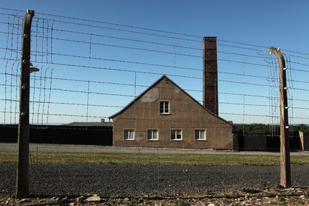 kz: WEIMAR, GERMANY - JUNE 21, 2013: Crematorium and electrified barbed wires in the Buchenwald concentration camp near Weimar, Germany.