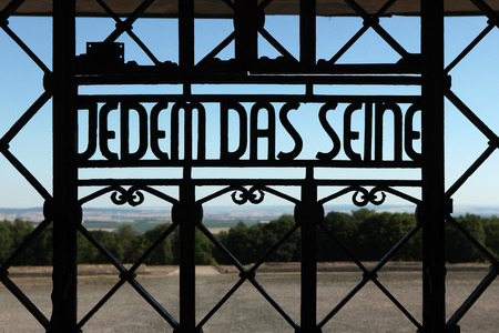 kz: WEIMAR, GERMANY - JUNE 21, 2013: Notorious Nazi motto Jedem das Seine (To Each His Own) seen on the main gate of the Buchenwald concentration camp near Weimar, Germany.