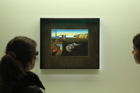 surrealist: PARIS, FRANCE - JANUARY 7, 2013: Visitors look at the painting The Persistence of Memory (1931) by Spanish surrealist artist Salvador Dali displayed at his retrospective exhibition in the Pompidou Centre in Paris, France.