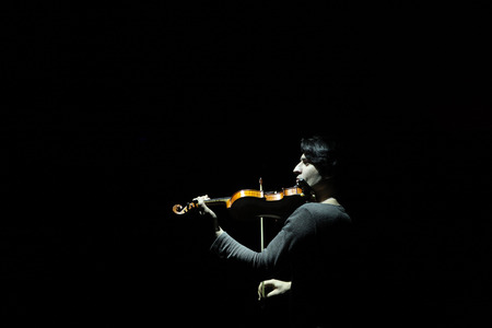 DRESDEN, GERMANY - MARCH 30, 2014: Talented Armenian violinist Edgar Hakobyan performs with Russian Grand Circus in Dresden, Germany, on March 30, 2014.