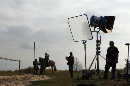 outside shooting: MILOVICE, CZECH REPUBLIC - OCTOBER 23, 2013: Actor dressed as a medieval knight rides a horse during the filming of the new movie The Knights directed by Carsten Gutschmidt near Milovice, Czech Republic.