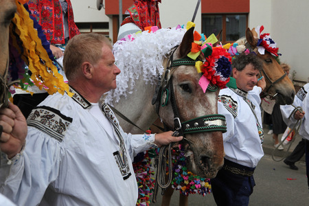 VLCNOV, CZECH REPUBLIC - MAY 26, 2013: Elderly men dressed in traditional Moravian folk costume lead decorated horses during the Ride of the Kings folklore festival in Vlcnov, South Moravia, Czech Republic.