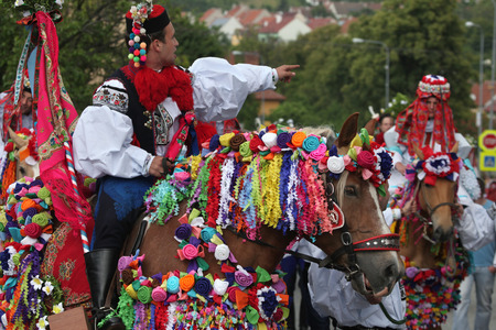 VLCNOV, CZECH REPUBLIC - MAY 26, 2013: Young men dressed in traditional Moravian folk costume ride decorated horses to perform the Recruits during the Ride of the Kings folklore festival in Vlcnov, South Moravia, Czech Republic. Redakční