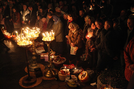 believers: PRAGUE, CZECH REPUBLIC - MAY 5, 2013: Orthodox believers pray during an Orthodox Easter night service in front of the Dormition Church at the Olsany Cemetery in Prague, Czech Republic.