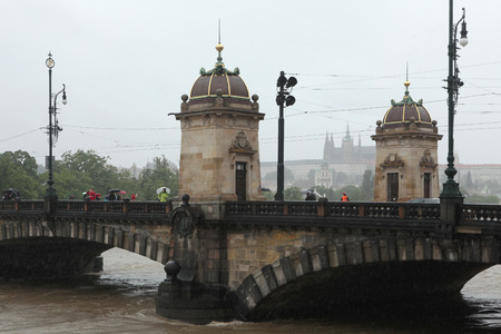 legion: PRAGUE, CZECH REPUBLIC - JUNE 3, 2013: People observe the rising water from the Legion Bridge partially flooded by the swollen Vltava River in Prague, Czech Republic. Prague Castle with St Vitus Cathedral is seen in the background.