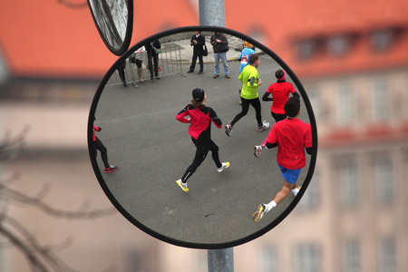 convex: PRAGUE, CZECH REPUBLIC - APRIL 6, 2013: Convex mirror with the reflection of athletes running the Prague international marathon in Prague, Czech Republic. Editorial