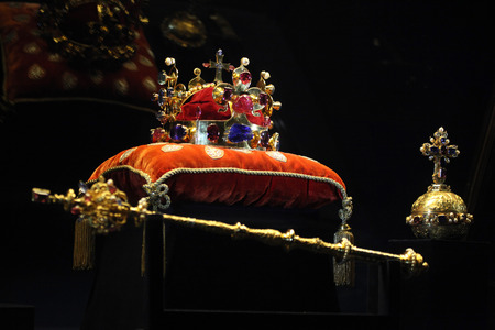 PRAGUE, CZECH REPUBLIC - MAY 10, 2013: Crown of Saint Wenceslas and the Royal Apple and Sceptre displayed at the exhibition of the Bohemian Crown Jewels in Prague, Czech Republic.