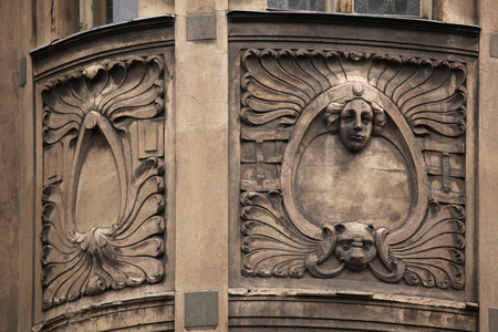 heads old building facade: Floral ornamental decoration and mascaron on the the Art Nouveau building in Prague, Czech Republic.