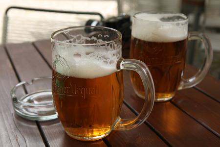 beerhouse: PRAGUE, CZECH REPUBLIC - MAY 13, 2014: Two mugs of traditional Czech beer Pilsner Urquell seen in a pub in Prague, Czech Republic. Editorial