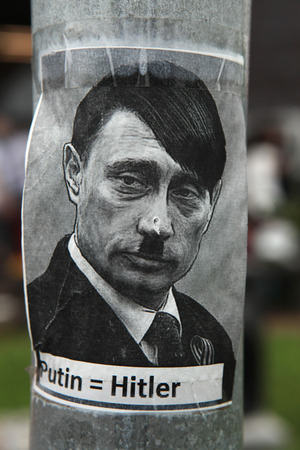 equals: PRAGUE, CZECH REPUBLIC - MAY 24, 2014: Sticker depicting Russian president Vladimir Putin as Adolf Hitler and with an equals sign between their names seen in Prague, Czech Republic.