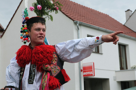 VLCNOV, CZECH REPUBLIC - MAY 26, 2013: Young man dressed in traditional Moravian folk costume performs the Recruit during the Ride of the Kings folklore festival in Vlcnov, South Moravia, Czech Republic. Redakční