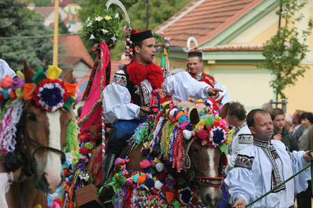VLCNOV, CZECH REPUBLIC - MAY 26, 2013: Young men dressed in traditional Moravian folk costume ride decorated horses to perform the Recruits during the Ride of the Kings folklore festival in Vlcnov, South Moravia, Czech Republic. Reklamní fotografie - 36221598