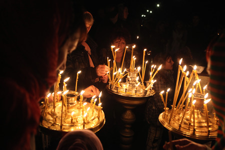 believers: PRAGUE, CZECH REPUBLIC - MAY 5, 2013: Orthodox believers light candles during an Orthodox Easter night service in front of the Dormition Church at the Olsany Cemetery in Prague, Czech Republic.