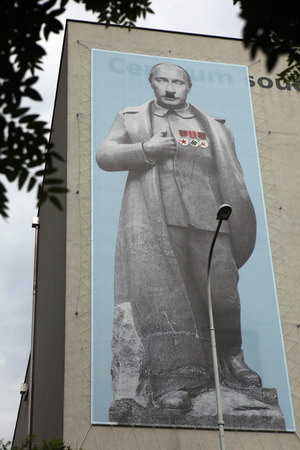 adolf hitler: PRAGUE, CZECH REPUBLIC - JUNE 13, 2014: Huge banner depicted Russian president Vladimir Putin dressed as Soviet dictator Josef Stalin and with Adolf Hitler toothbrush moustache on the facade of the DOX Centre for Contemporary Art in Prague, Czech Republic Editorial