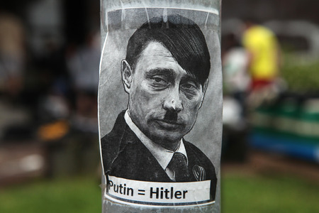 adolf: PRAGUE, CZECH REPUBLIC - MAY 24, 2014: Sticker depicting Russian president Vladimir Putin as Adolf Hitler and with an equals sign between their names seen in Prague, Czech Republic.